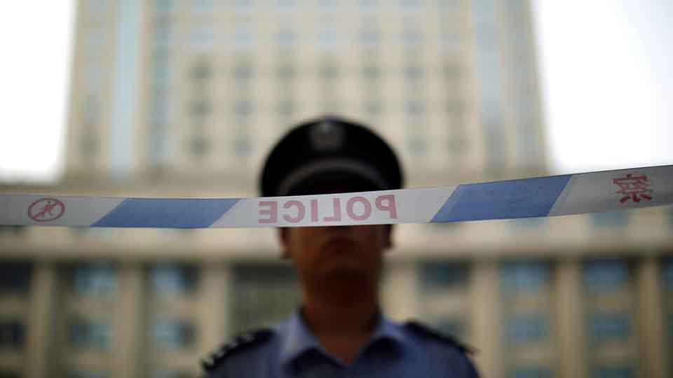 A police officer stands guard at the entrance to the Jinan Intermediate People's Court on the third day of the trial of ousted Chinese politician Bo Xilai in Jinan, Shandong province August 24, 2013.