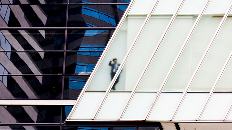 A businessman stands behind a frosted glass window of an office high-rise in central Tokyo June 9, 2015.