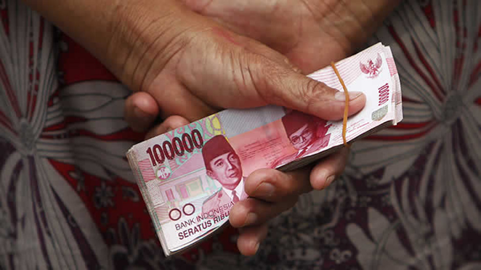 A woman holds Indonesian rupiah banknotes in front of a Bank Indonesia mobile bank